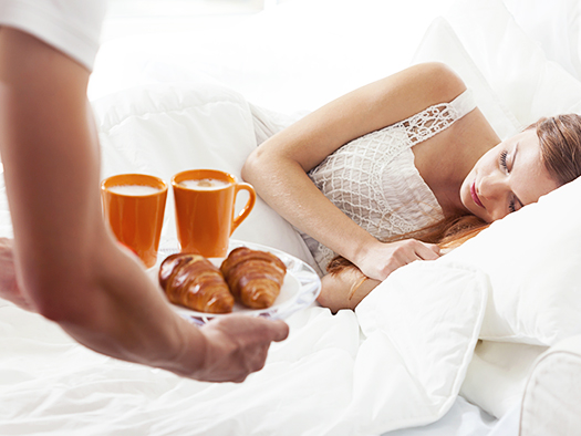 Men brings breakfast to bed